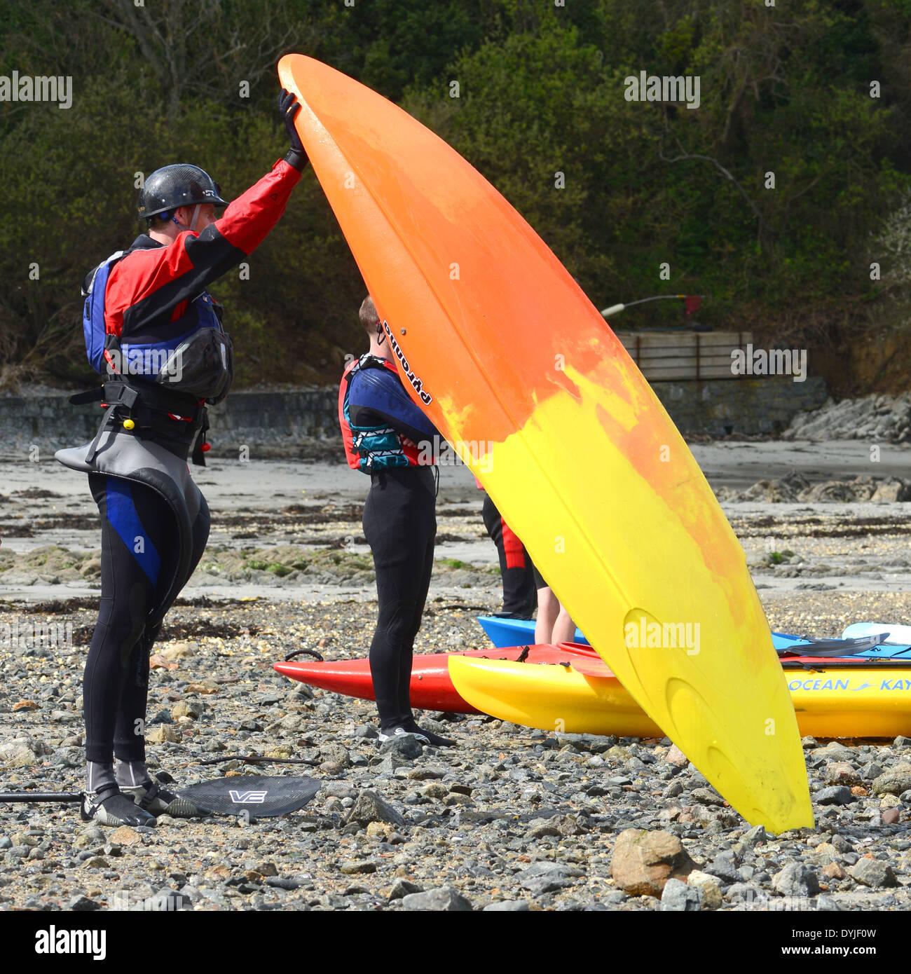 Man draining water out of kayak - Stock Image