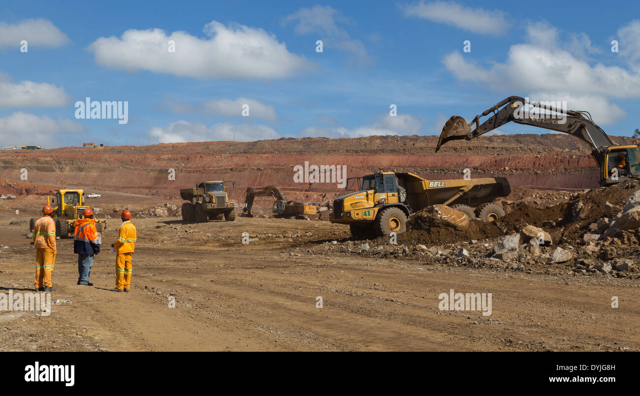 A supervisor directs workers during loading of trucks in a large open cast copper mine. - Stock Image