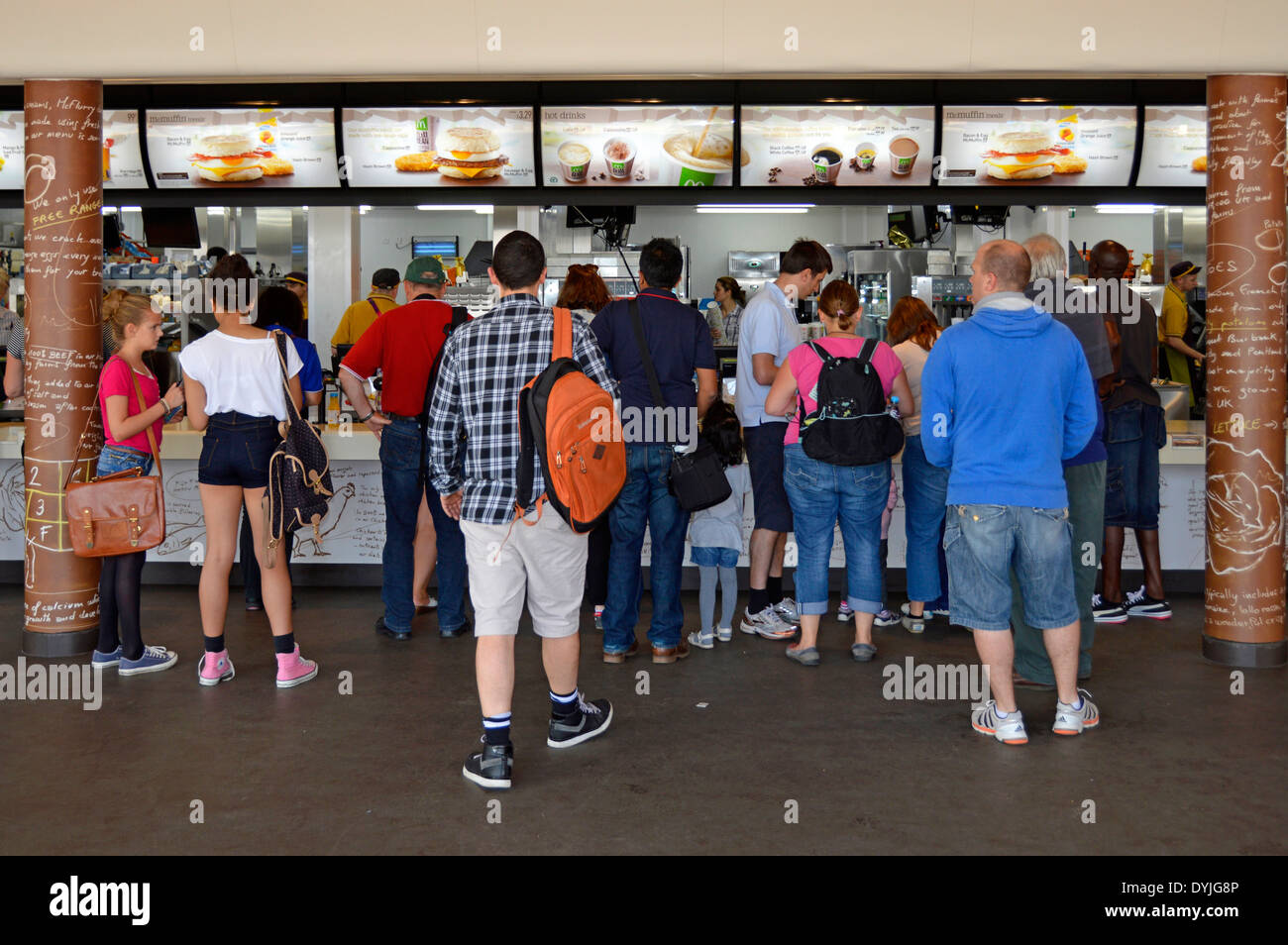 Interior view of McDonalds fast food restaurant people waiting at counter to be served London 2012 Olympic Park Stratford Newham London England UK - Stock Image