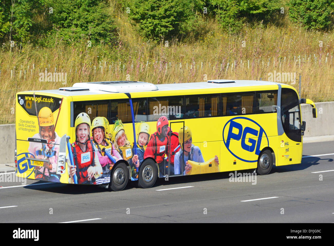 Advertising promoting adventure travel for school children on side and back of coach driving along motorway - Stock Image