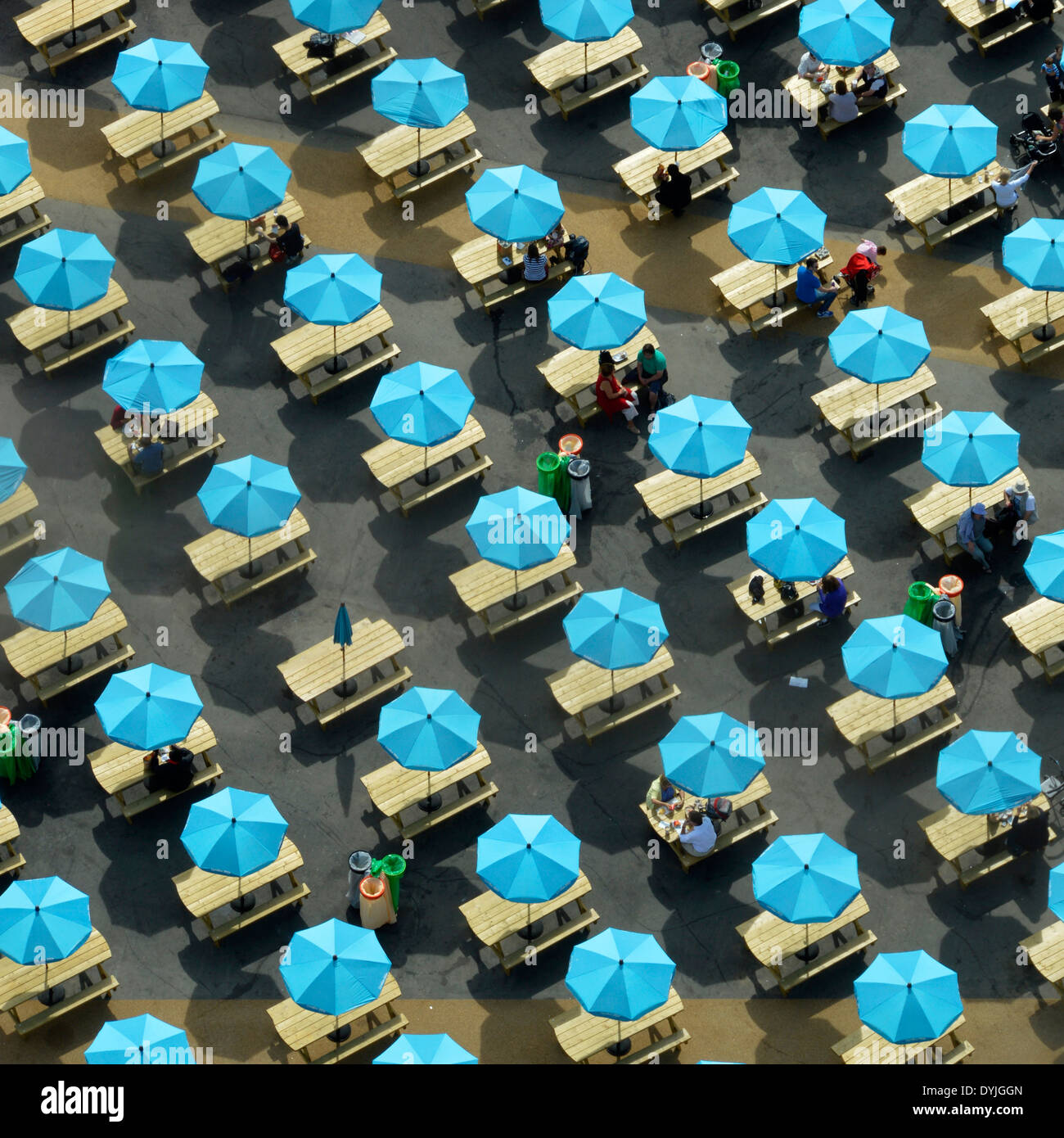 Colourful parasols shading picnic tables with one not open (odd one out) - Stock Image