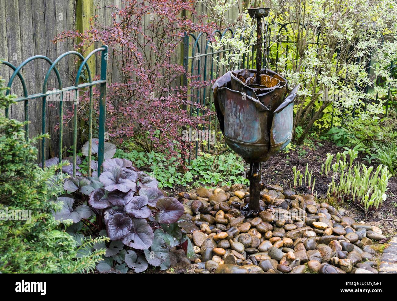Metal Flower Sculpture In Water Feature Garden, England UK