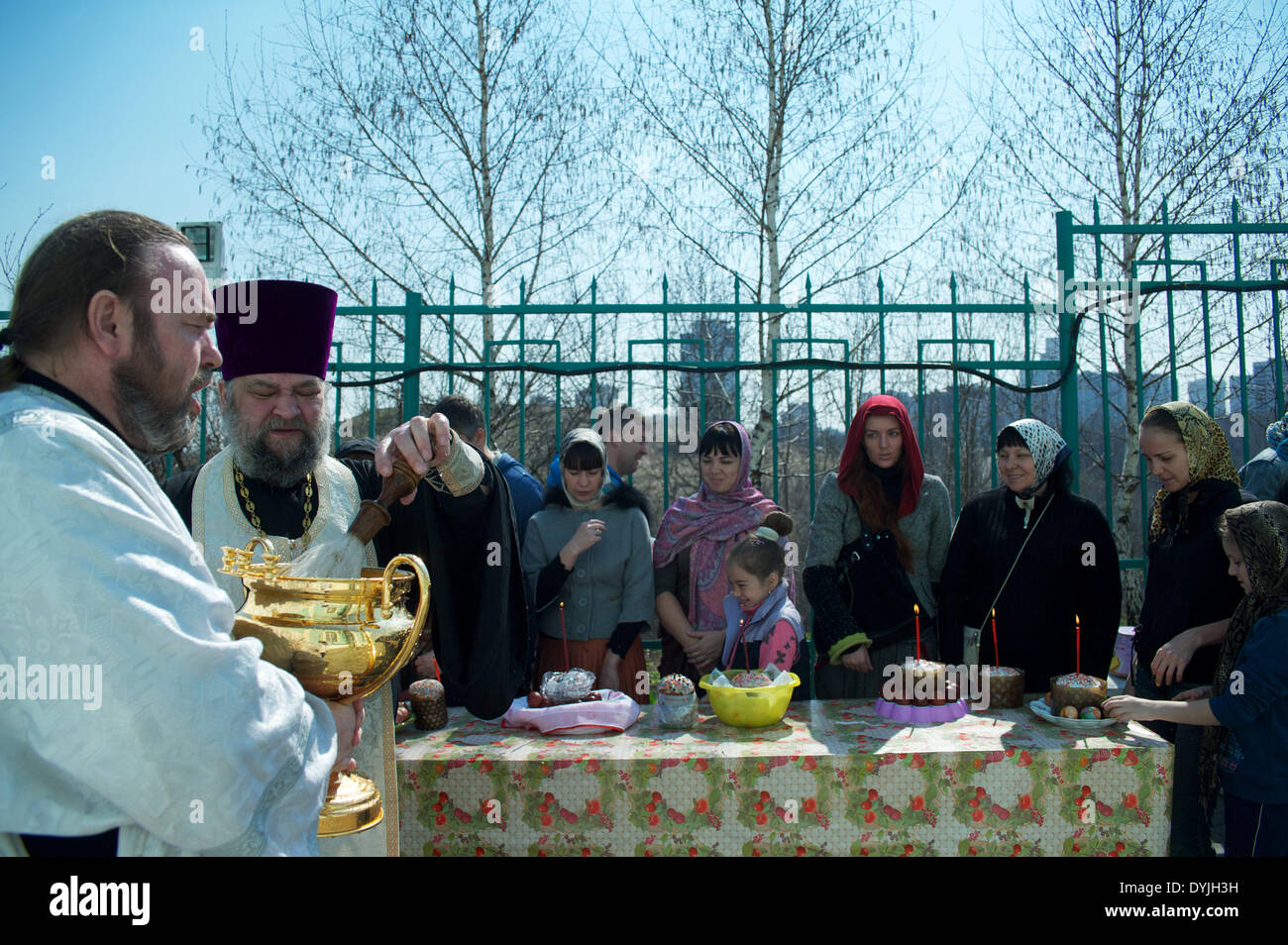 Moscow, Russia. 19th Apr, 2014. A Russian Orthodox priest blesses people and traditional Easter cakes and painted eggs prepared for an Easter celebration, near a church in Moscow. Credit:  Anna Sergeeva/ZUMAPRESS.com/Alamy Live News - Stock Image