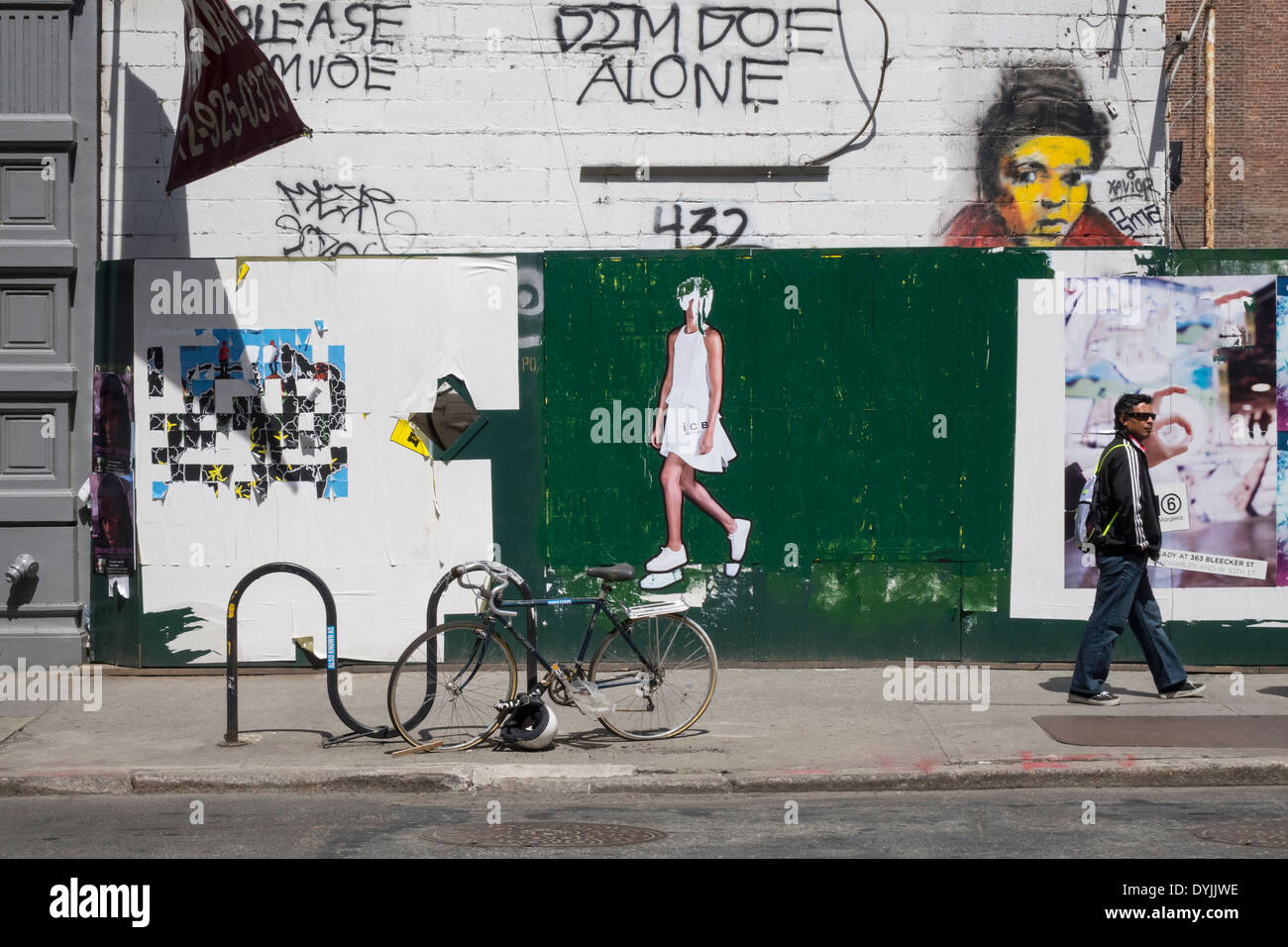 Graffiti and faded poster ads in New York City - Stock Image