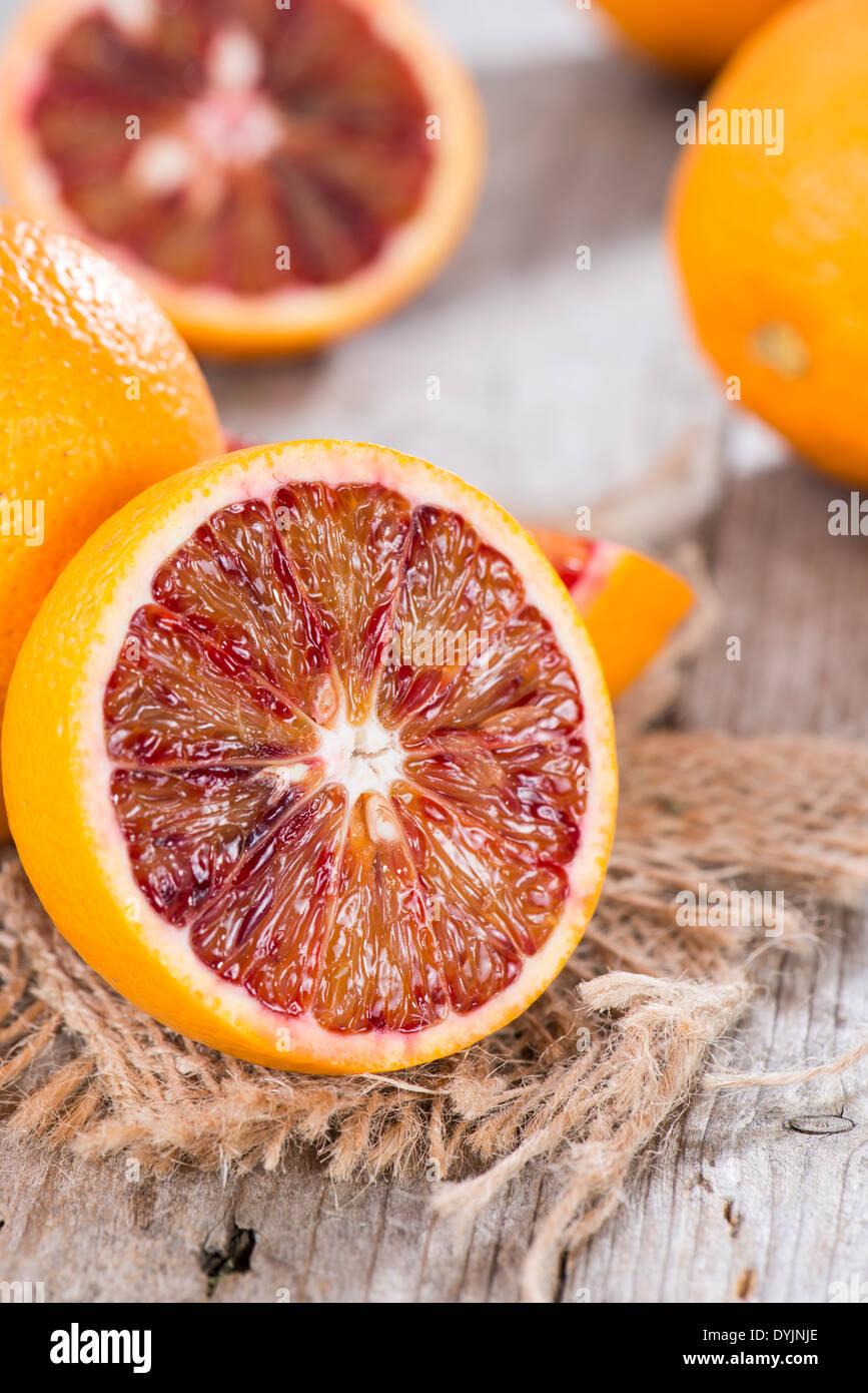 Some halved Blood Oranges (close-up shot) on wooden background - Stock Image
