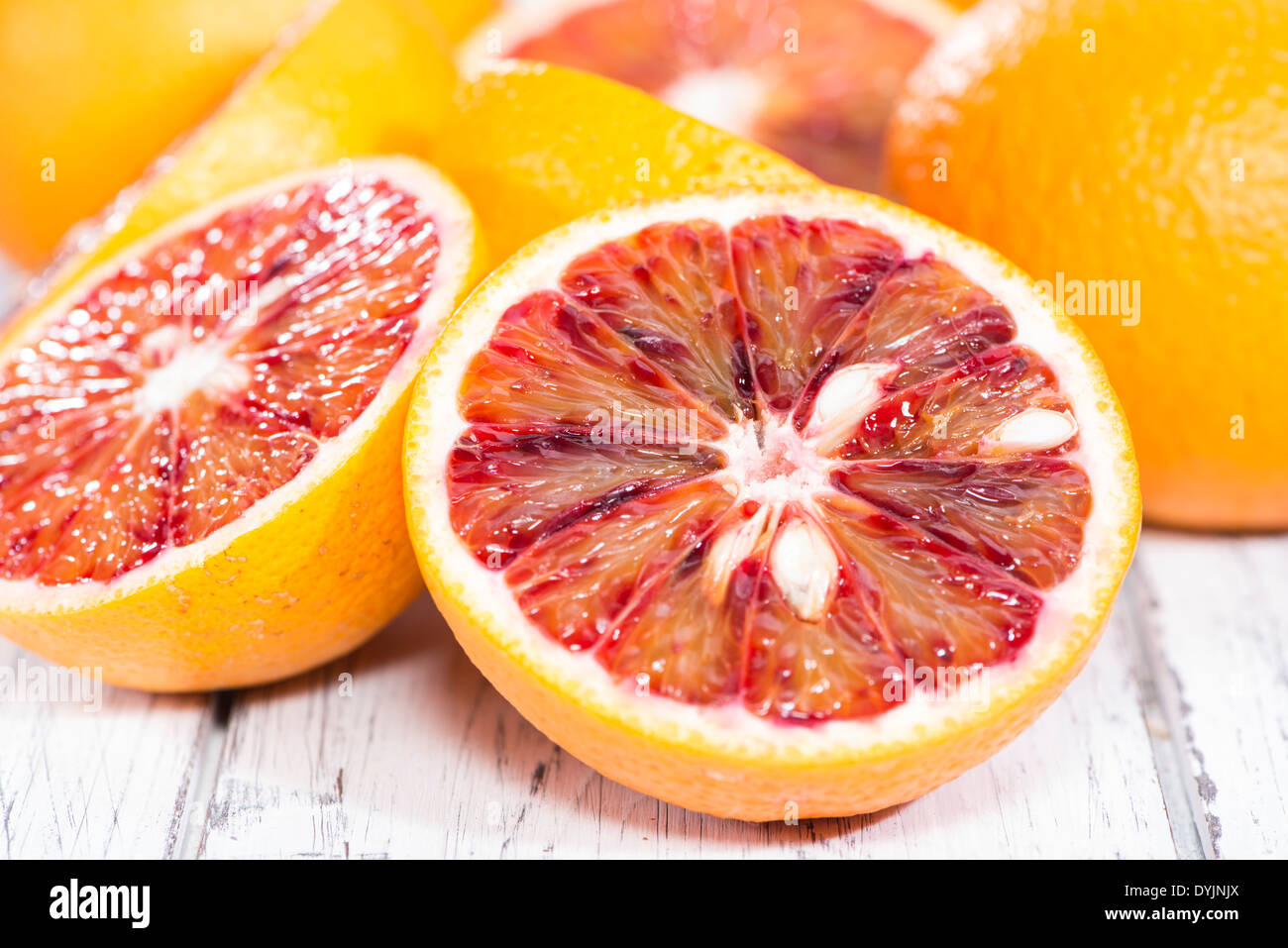 Some halved Blood Oranges (close-up shot) on wooden background - Stock Image