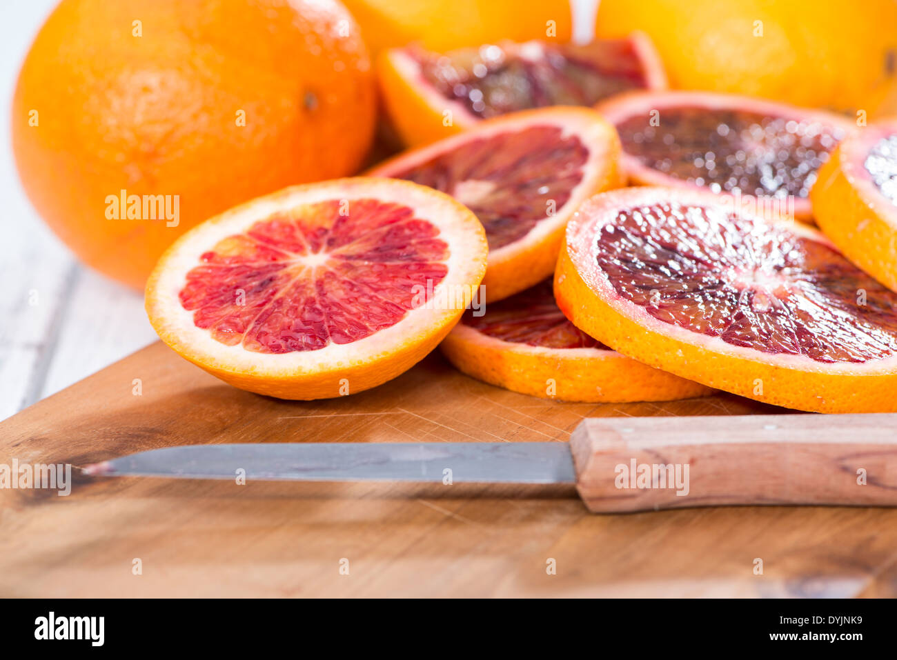Portion of fresh and juicy Blood Orange on wooden background - Stock Image