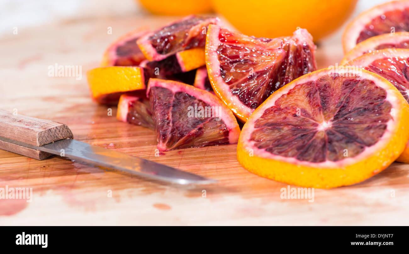 Blood Orange pieces on wooden background (close-up studio shot) - Stock Image