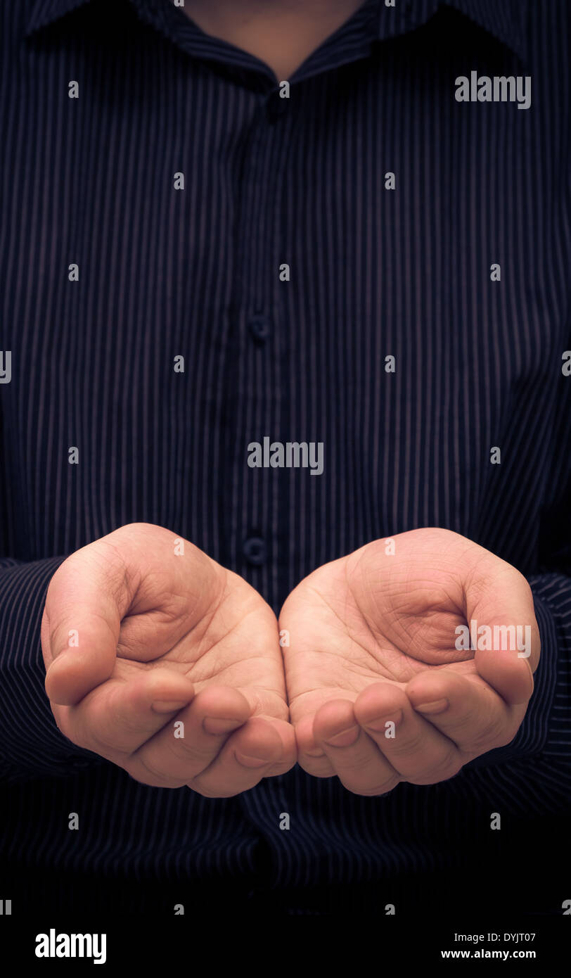 The man's hands in a gesture of holding something or ask for help - Stock Image