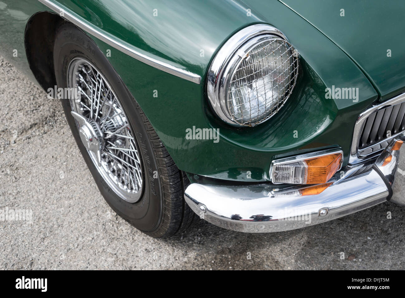 Front wing detail classic British Racing Green 1966 MG-B roadster sports car showing stone guard on headlamp and wire wheel - Stock Image