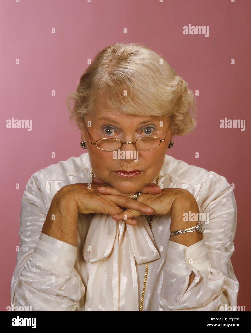 Nachdenkliche Oma stützt den Kopf auf die Hände Pensive