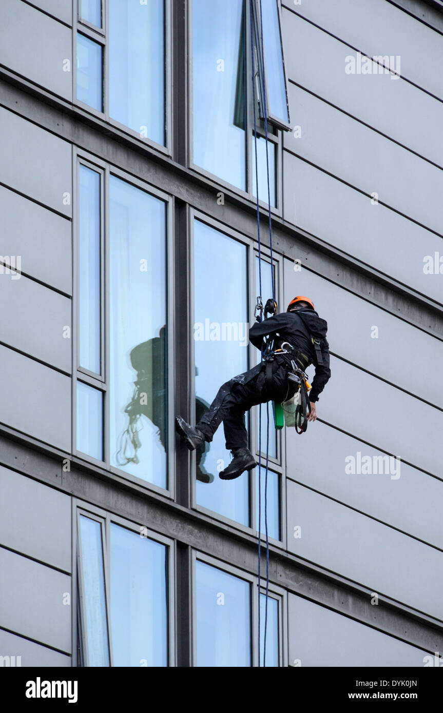 Window cleaner using industrial rope access techniques at work on an office building, London Road, Manchester, England, UK - Stock Image