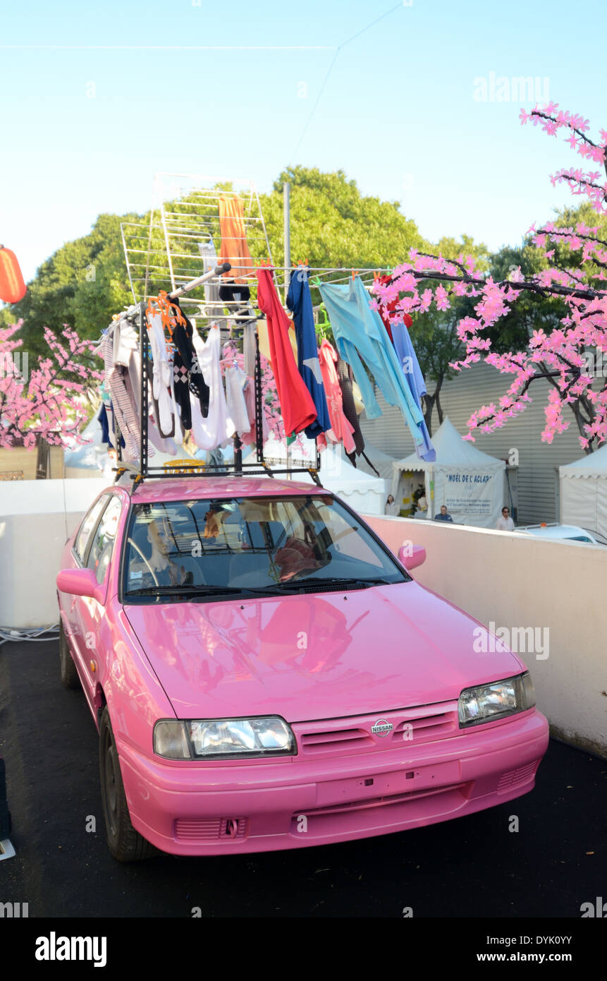 Pink Nissan Car Pink Blossom & Portable Clothes Drier Attached to Car. Useless Japanese Gadget or Chindogu. - Stock Image
