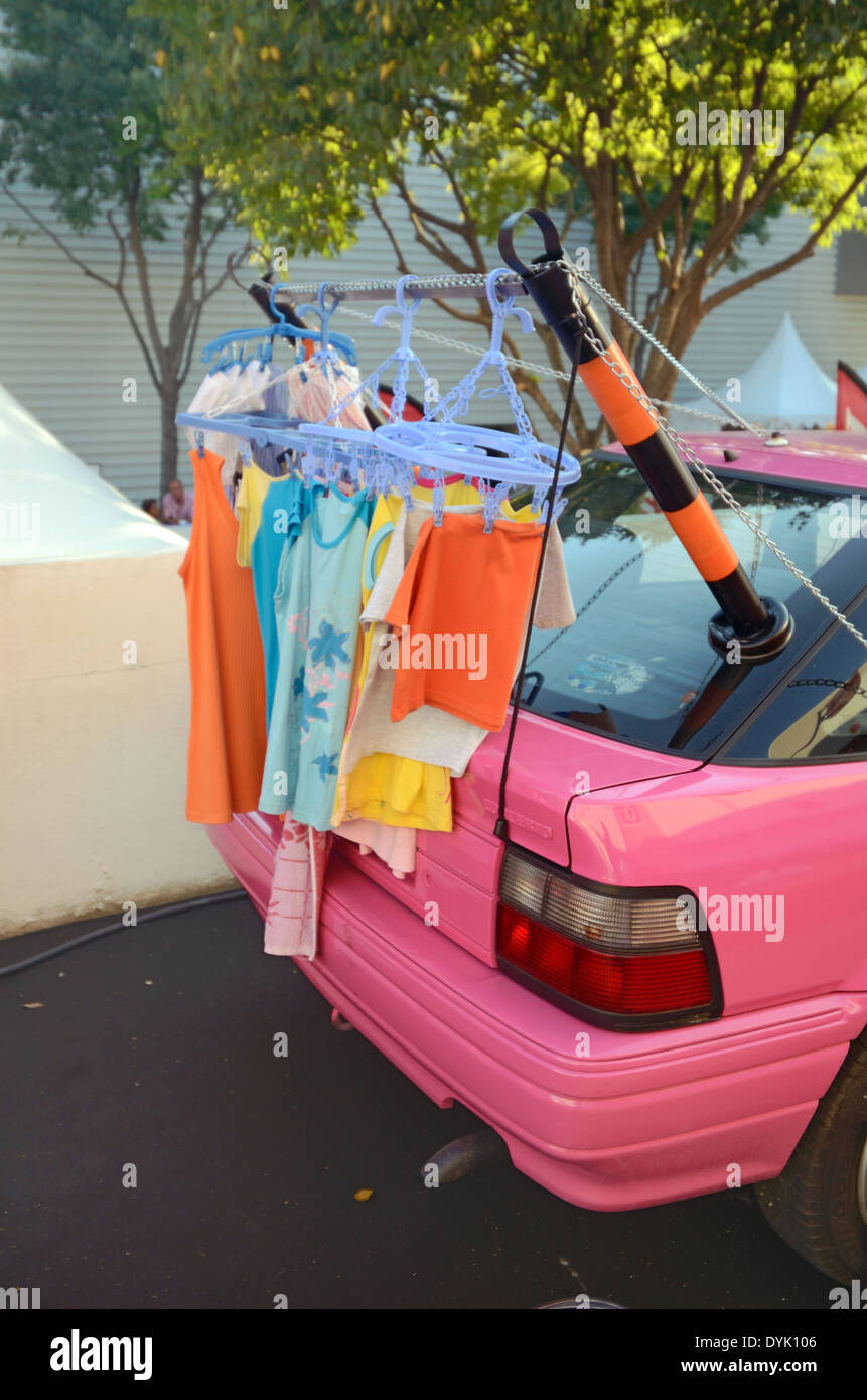 Portable Clothes Drier or Line Attached to on a Pink Nissan Car. Useless Japanese Gadget or Chindogu. - Stock Image