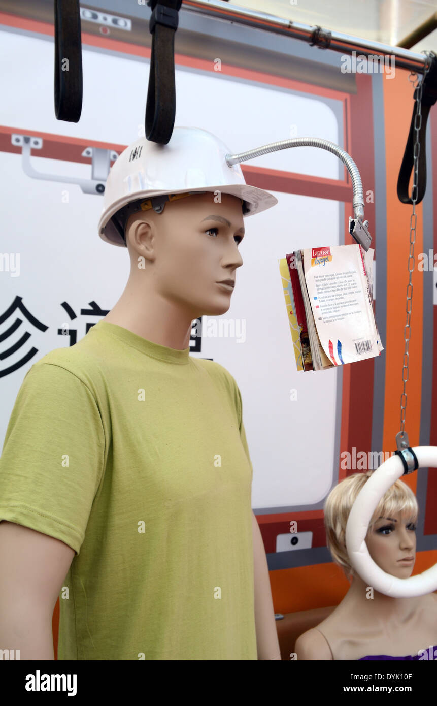 Male Train Passenger or Dummy Wearing Hard Helmet with Book Holder in Train. Useless Japanese Gadget or Chindogu. - Stock Image