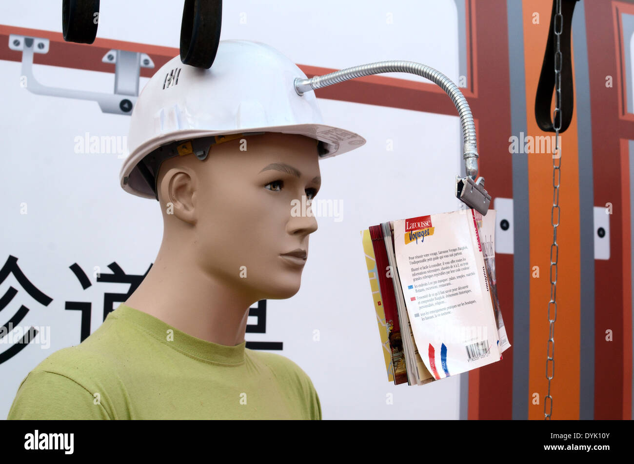 Male Train Passenger or Dummy Wearing Hard Helmet Gadget with Book Holder on Train. Useless Japanese Gadget or Chindogu - Stock Image
