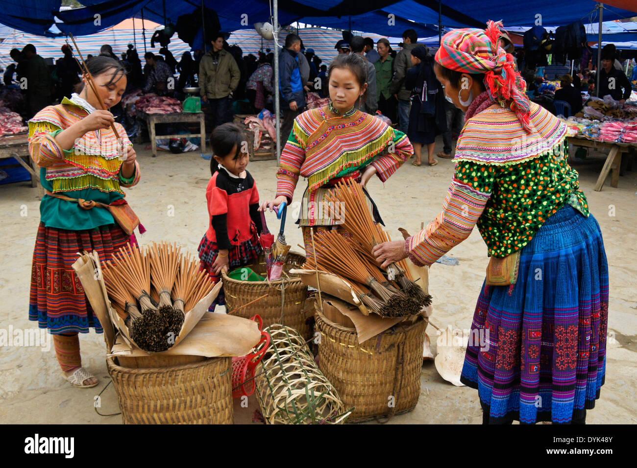 Flower Hmong women and children selling incense at Sunday market, Bac Ha, Sapa (Sa Pa), North Vietnam - Stock Image