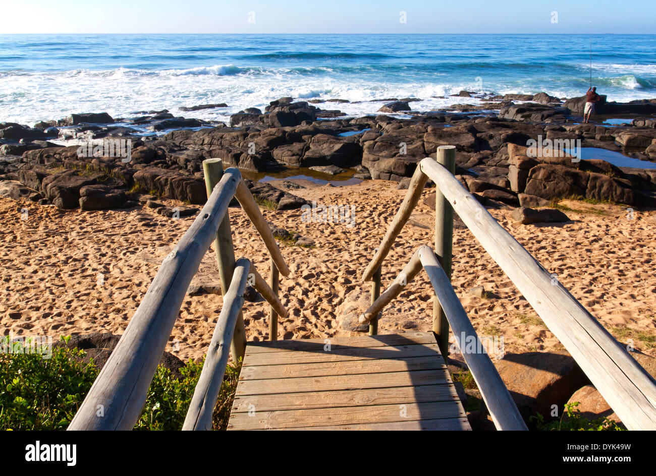 weathered wooden stairway leading onto rocky beach - Stock Image