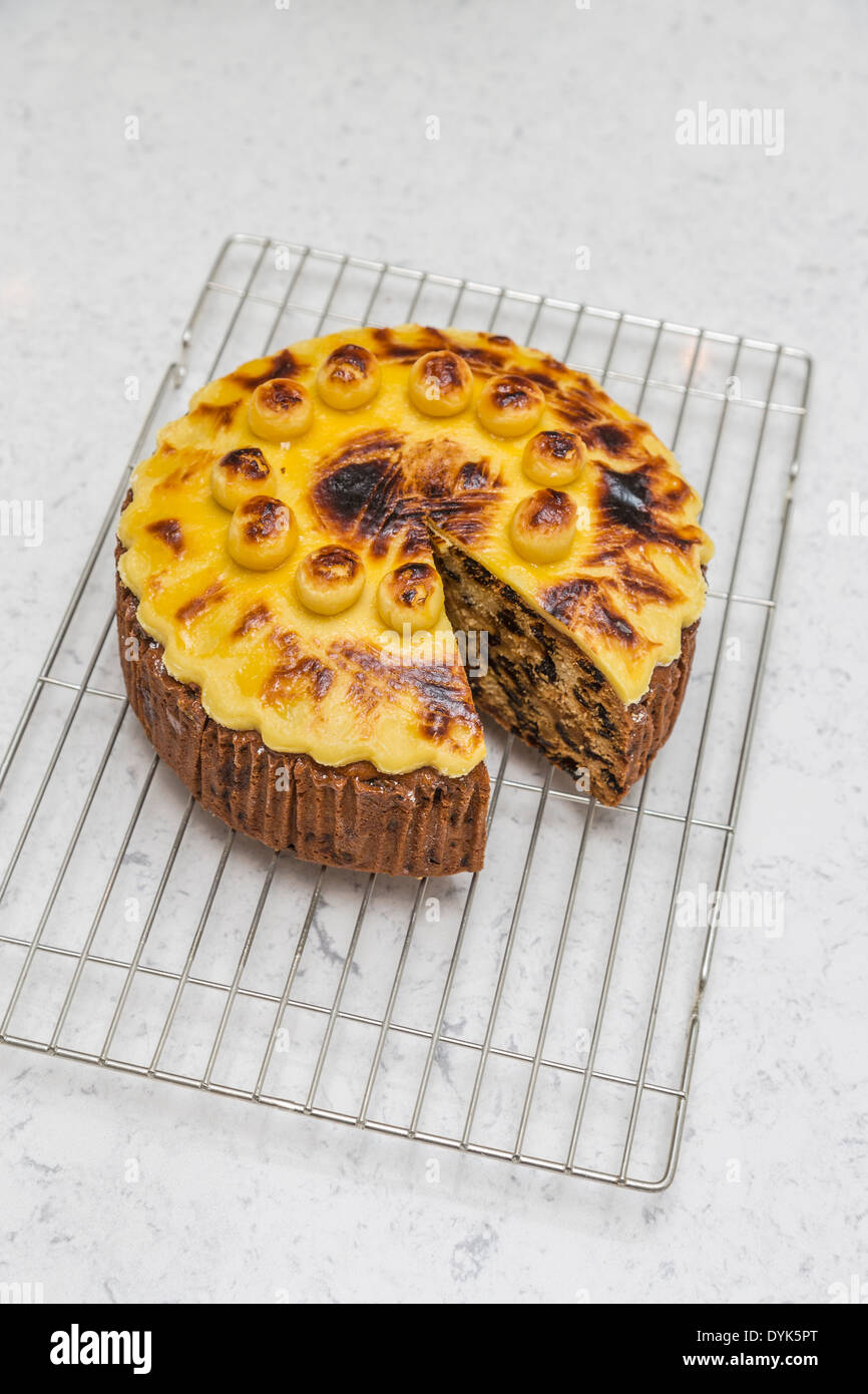 Traditional home baked round simnel cake for Easter, topped with marzipan, on wire baking rack Stock Photo