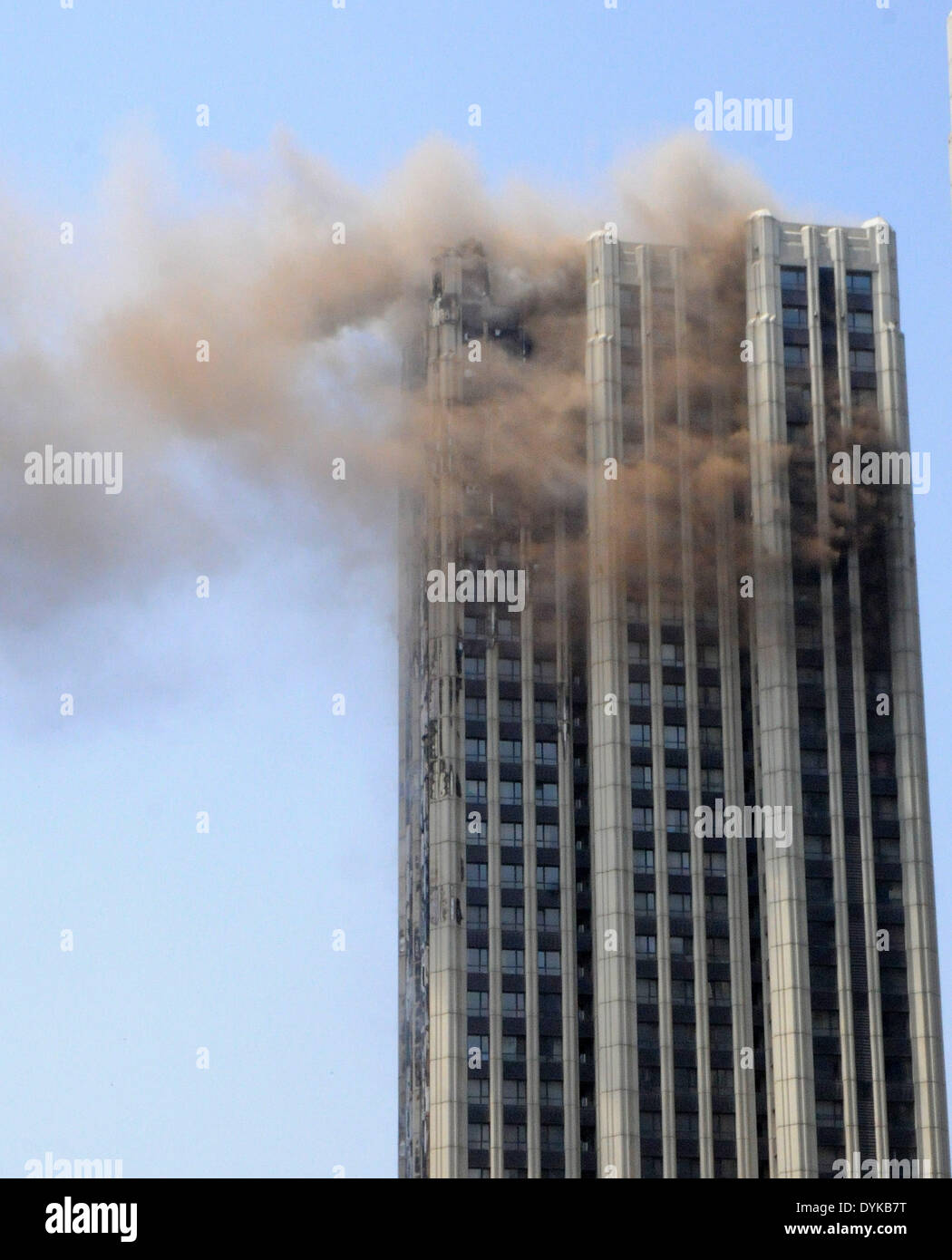 Dalian, China's Liaoning Province. 21st Apr, 2014. Insulating layers of a high-rise residential building is on fire at Xinghai Square in Dalian, northeast China's Liaoning Province, April 21, 2014. The fire, which was found at 11 a.m. on April 21, has been extinguished and no casualties were reported by far. Credit:  Cai Yongjun/Xinhua/Alamy Live News - Stock Image