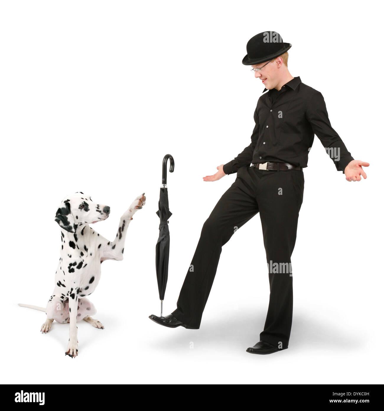 junger Mann mit Melone balanciert mit Schirm, young man with bowler hat balancing an umbrella, Mann spielt mit Dalmatiner Stock Photo