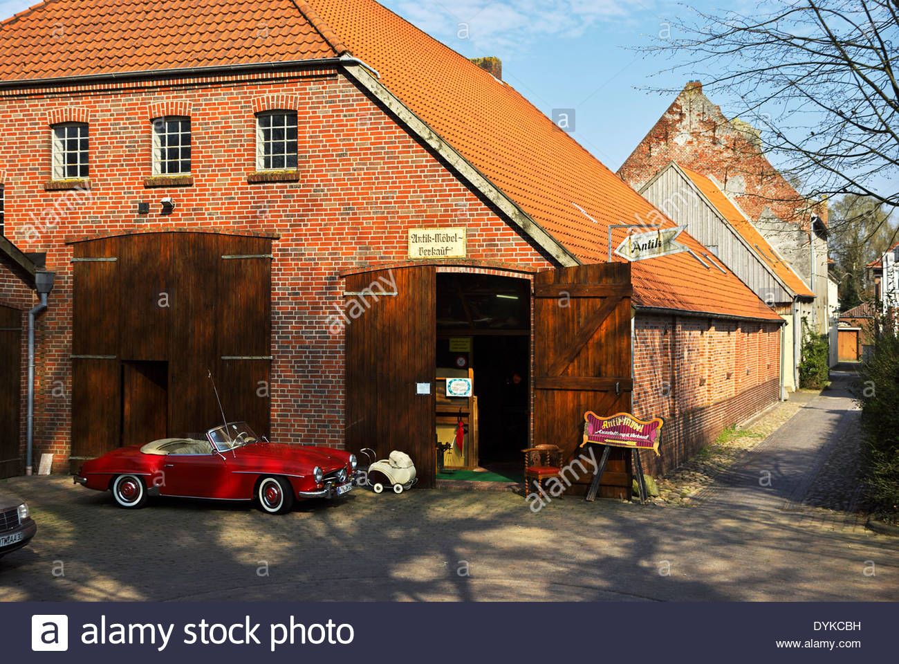 A vintage Mercedes Benz 190SL and a smaller buggy are parked in front of Antik-Möbel-Verkauf in Esens, Germany. - Stock Image