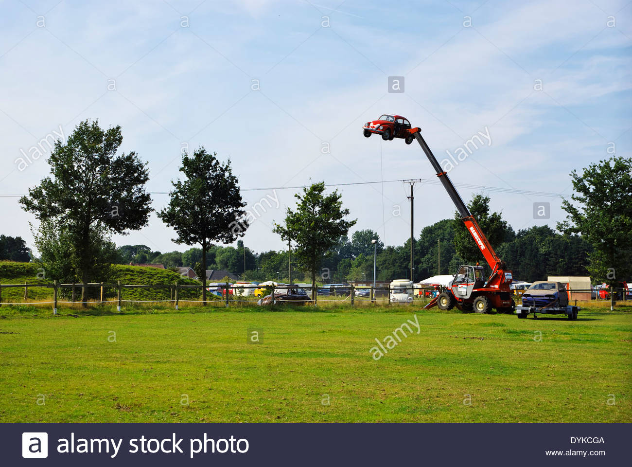 VW Bug is hoisted on Manitou Maniscopic lift at Käfer Verein (Beetle Club) gathering in Fürstenau, Lower Saxony, Germany. - Stock Image