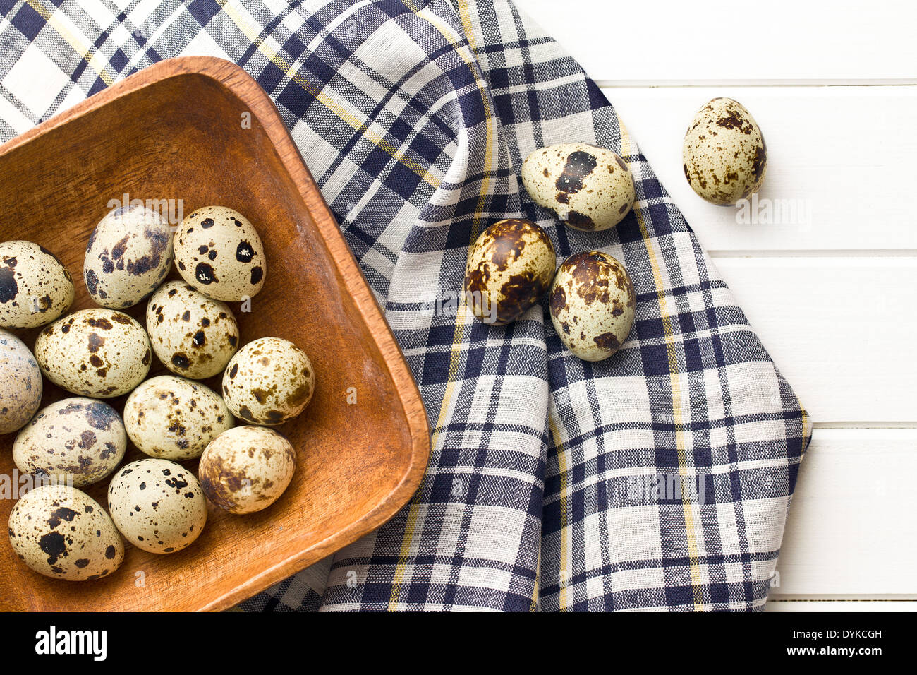 Quail eggs in wooden bowl on kitchen table - Stock Image