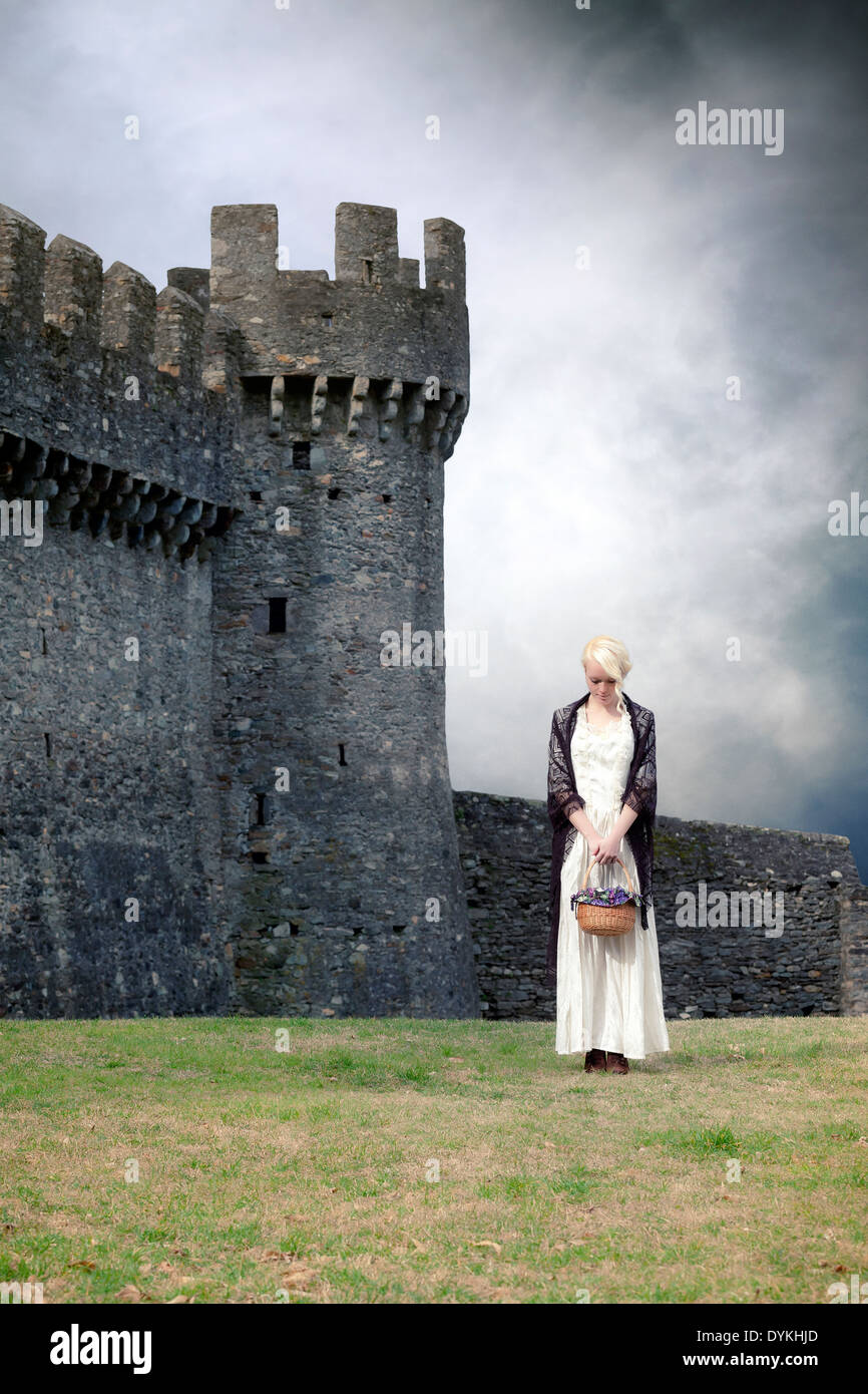 a woman in a white period dress is standing in front of a castle - Stock Image