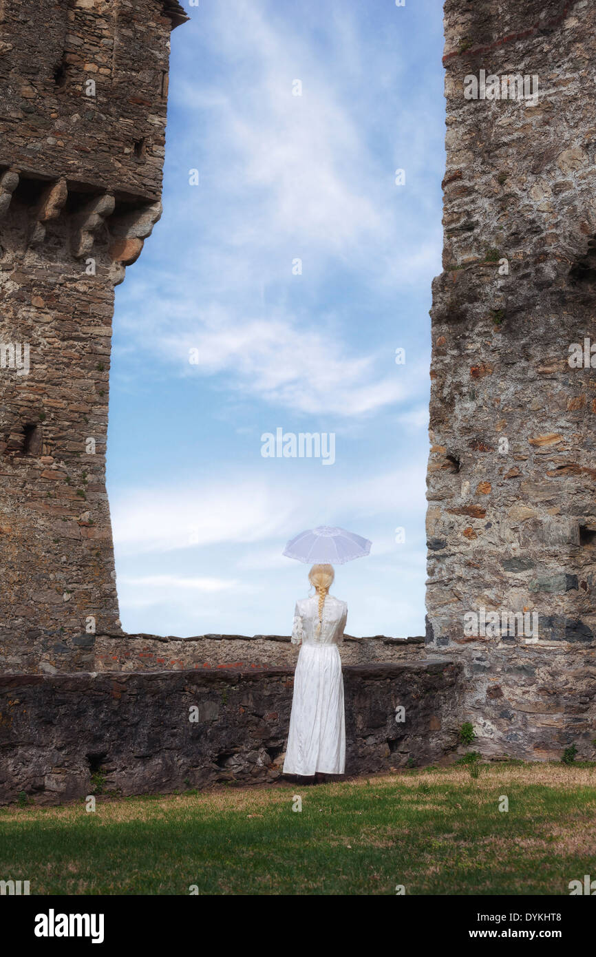 a woman in a white period dress is standing at a stone wall with a parasol - Stock Image