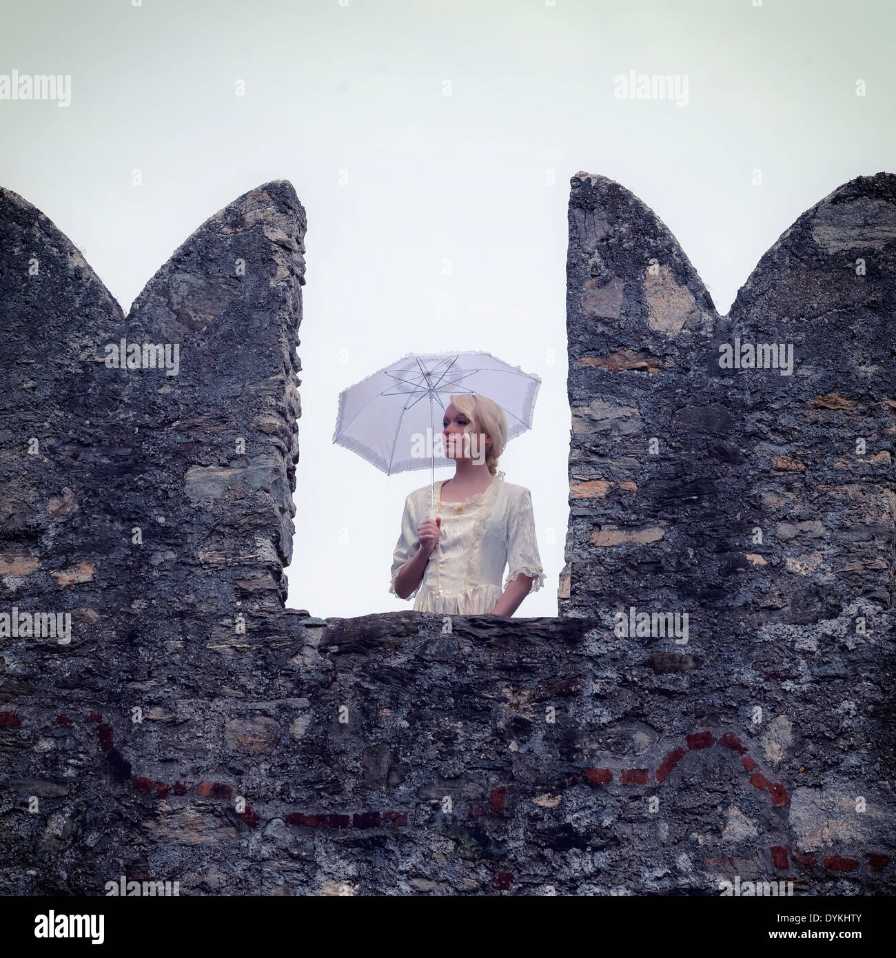 a lady with a white period dress is standing on a battlement - Stock Image