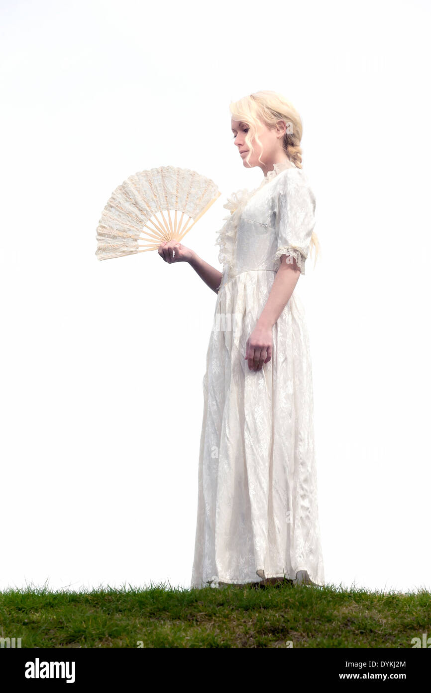 a lady in a white period dress with a lace fan - Stock Image