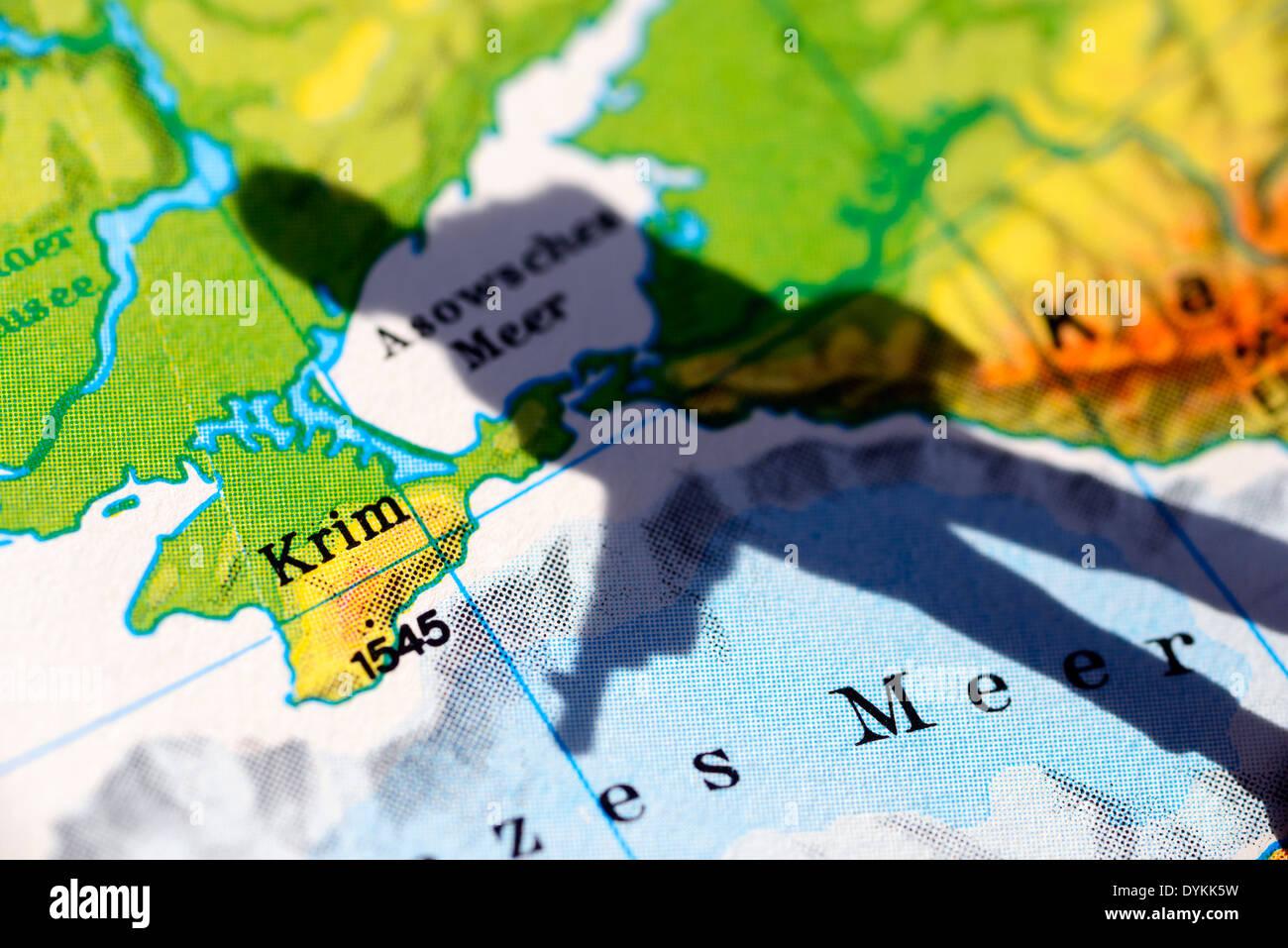 Die Krim auf einer Landkarte und Schatten eines Soldaten, Krim-Krise - Stock Image