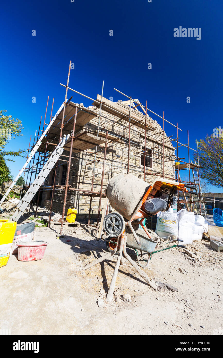 building site cement mixer new build building house home scaffold Yorkshire Dales National Park, UK England GB scaffolding - Stock Image