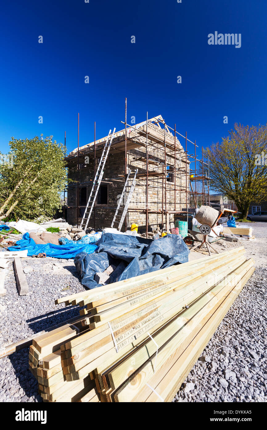building site timber wood new build building house home scaffold Yorkshire Dales National Park, UK England GB slats roofing - Stock Image