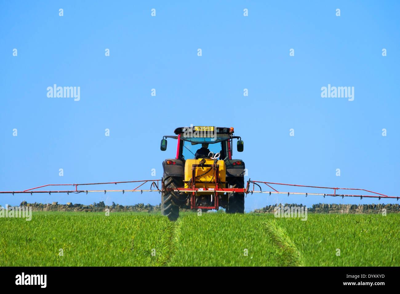 Farmer spraying crops near Thurstonland, Holme Valley, West Yorkshire, England, UK - Stock Image