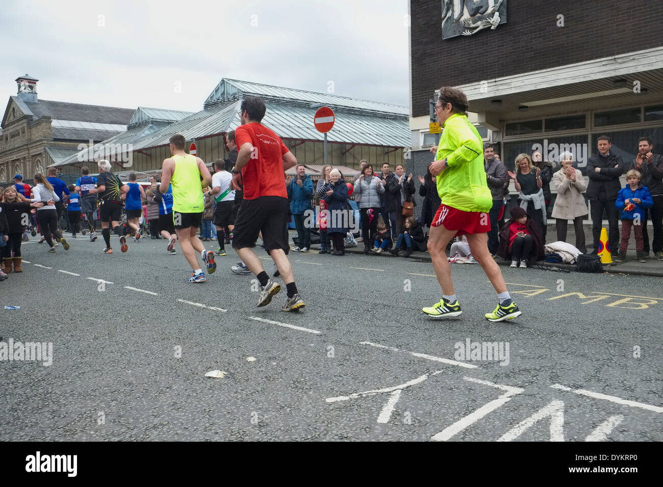 Runners reach the approximate half-way stage along Market Street, Altrincham in the 2014 Manchester Marathon. - Stock Image
