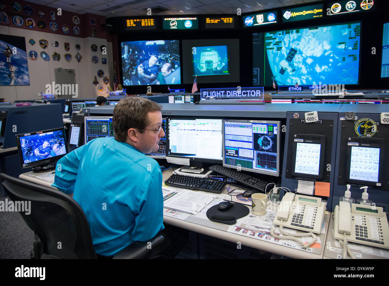 NASA Flight Director Matt Abbott monitors the SpaceX Dragon capsule cargo rendezvous and grappling with the International Space Station from the Mission Control Center space station flight control room April 20, 2014 in Houston, Texas. - Stock Image