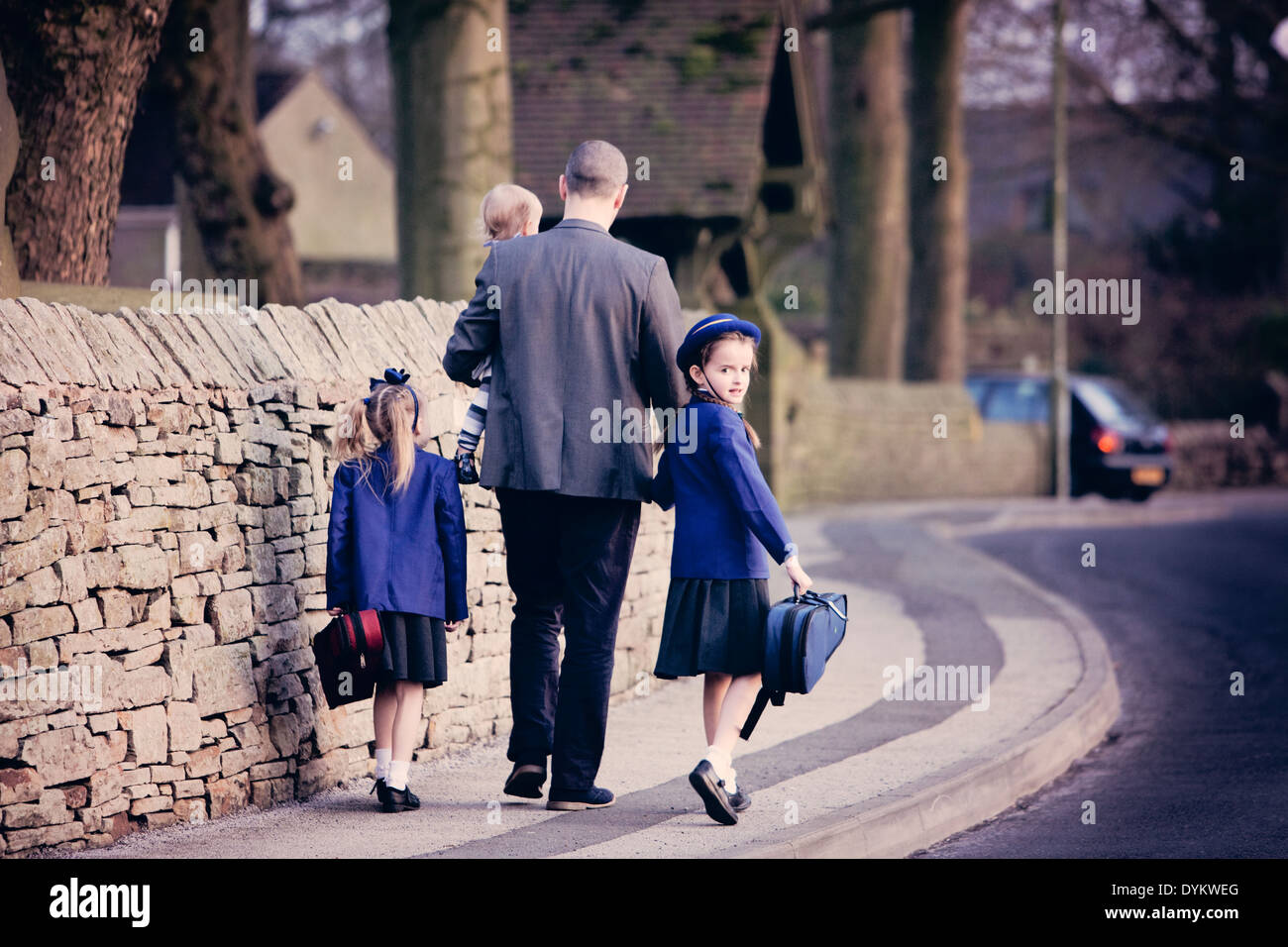 A smartly dressed father, holding hands with his children and walking them to school - Stock Image