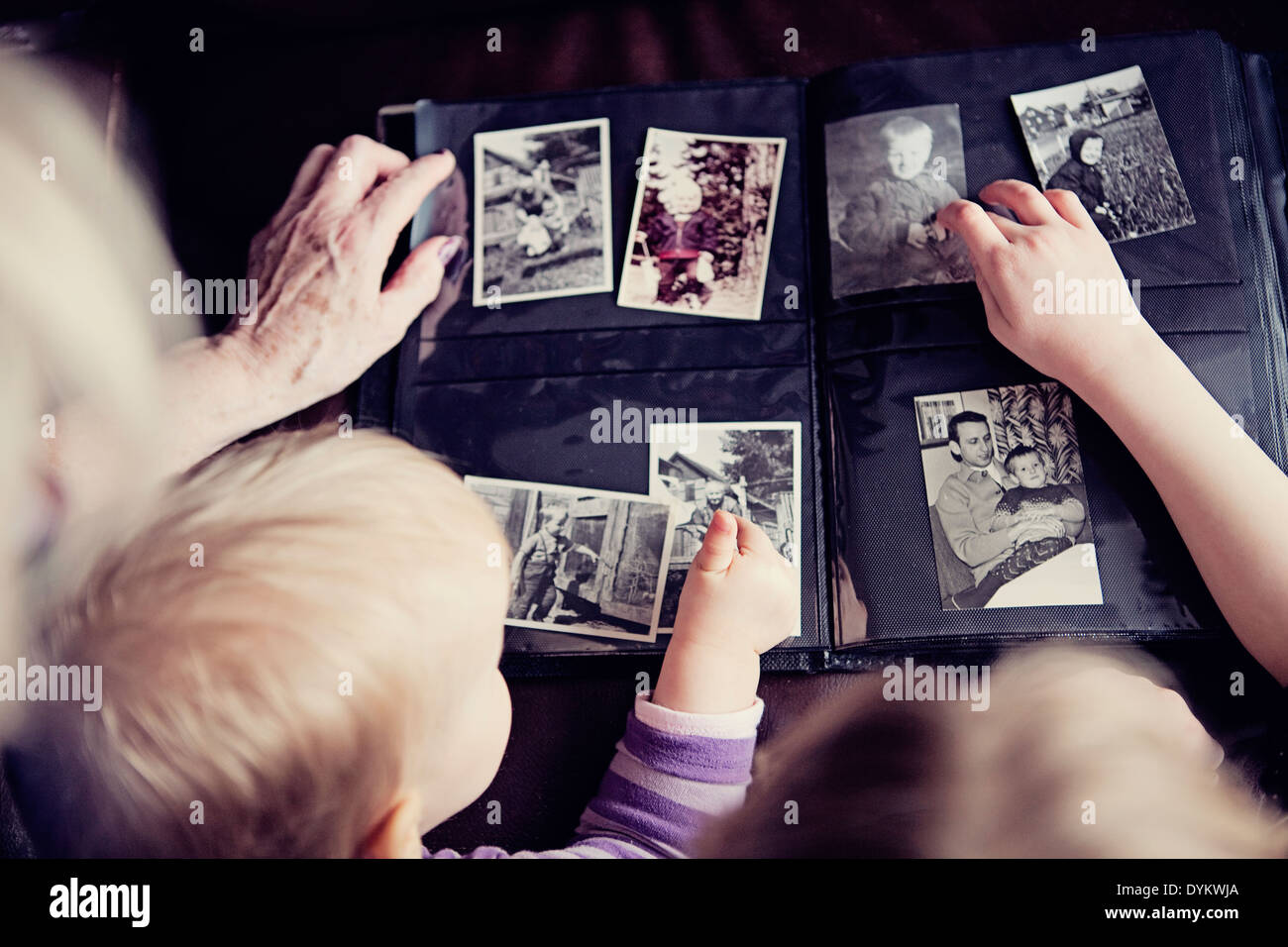 Generations of one family looking through an old family photo album together. - Stock Image