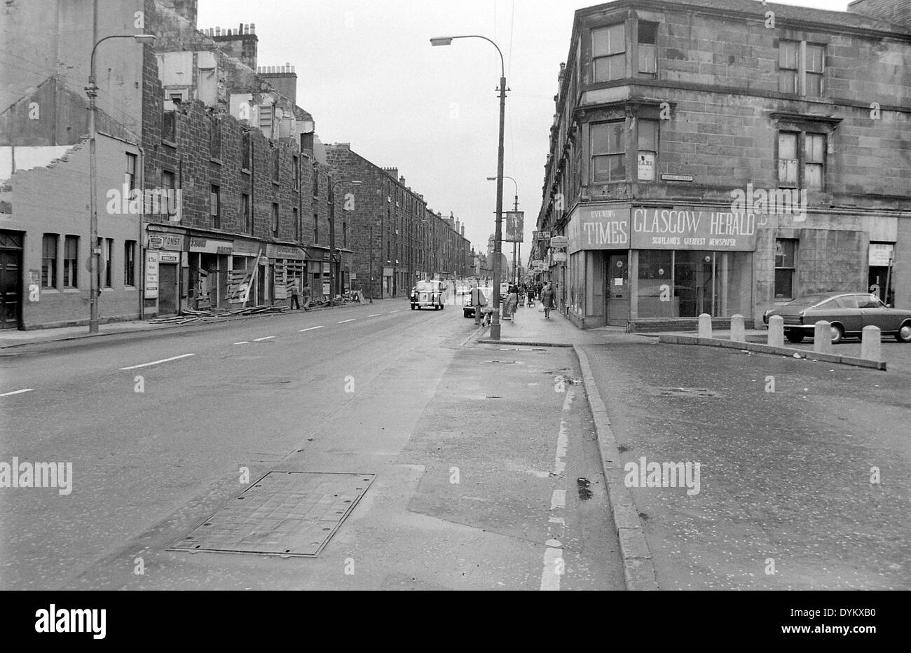 Looking down Glasgow road in Clydebank. John Brown's Shipyard gatehouse on the left,almost demolished, and the tenements also - Stock Image