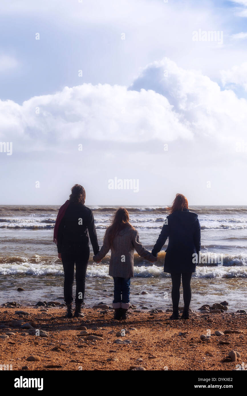 three girls hand in hand at the sea - Stock Image