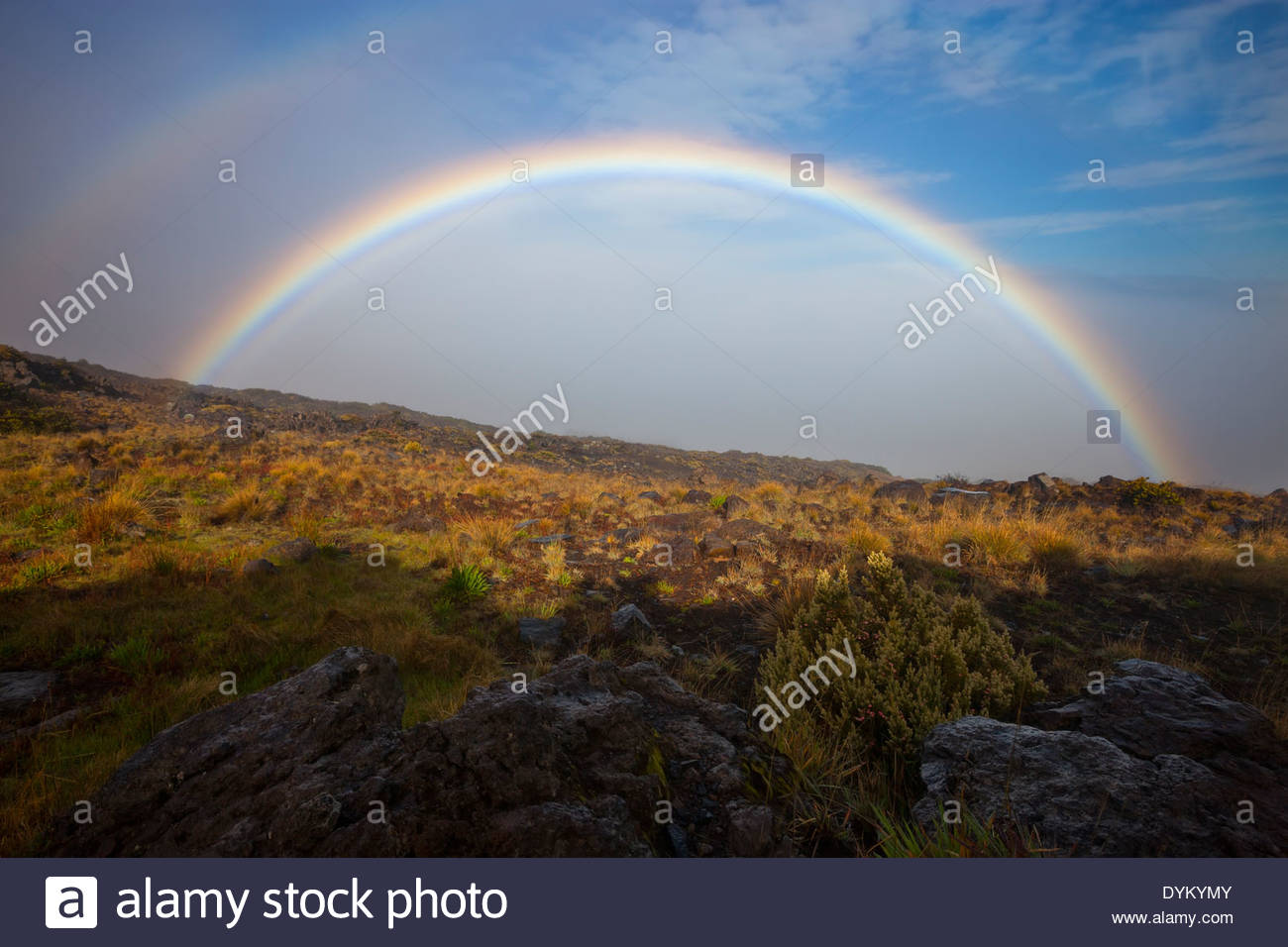 A bright rainbow stretches across the rugged eastern slope of the dormant Haleakalā volcano on the island of Maui, - Stock Image