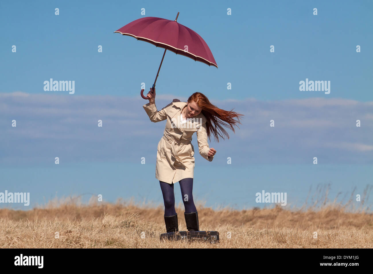 Red haired girl with vintage bag and umbrella Stock Photo