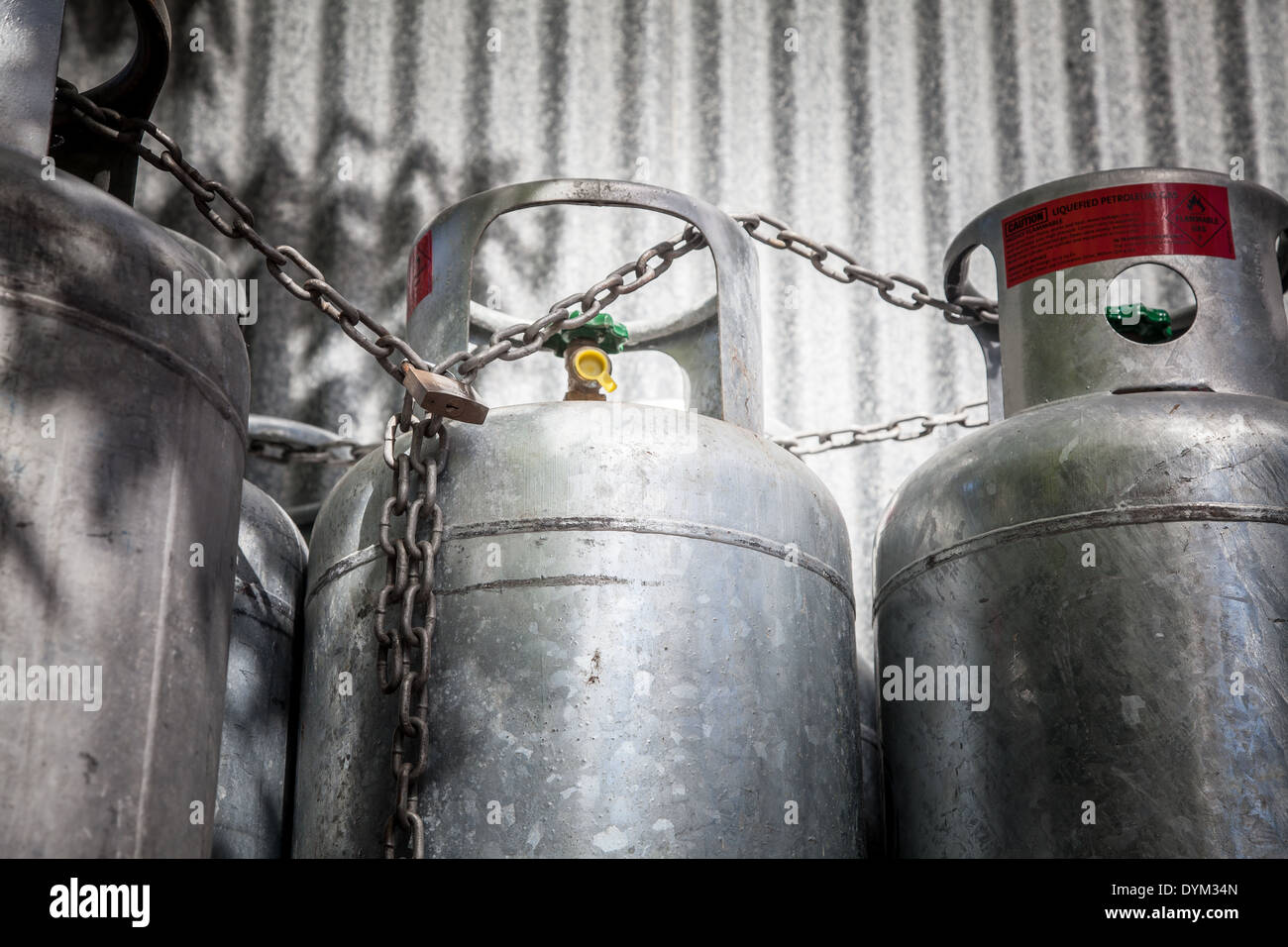 Some gas bottles chained and padlocked against a galvanized steel wall. - Stock Image