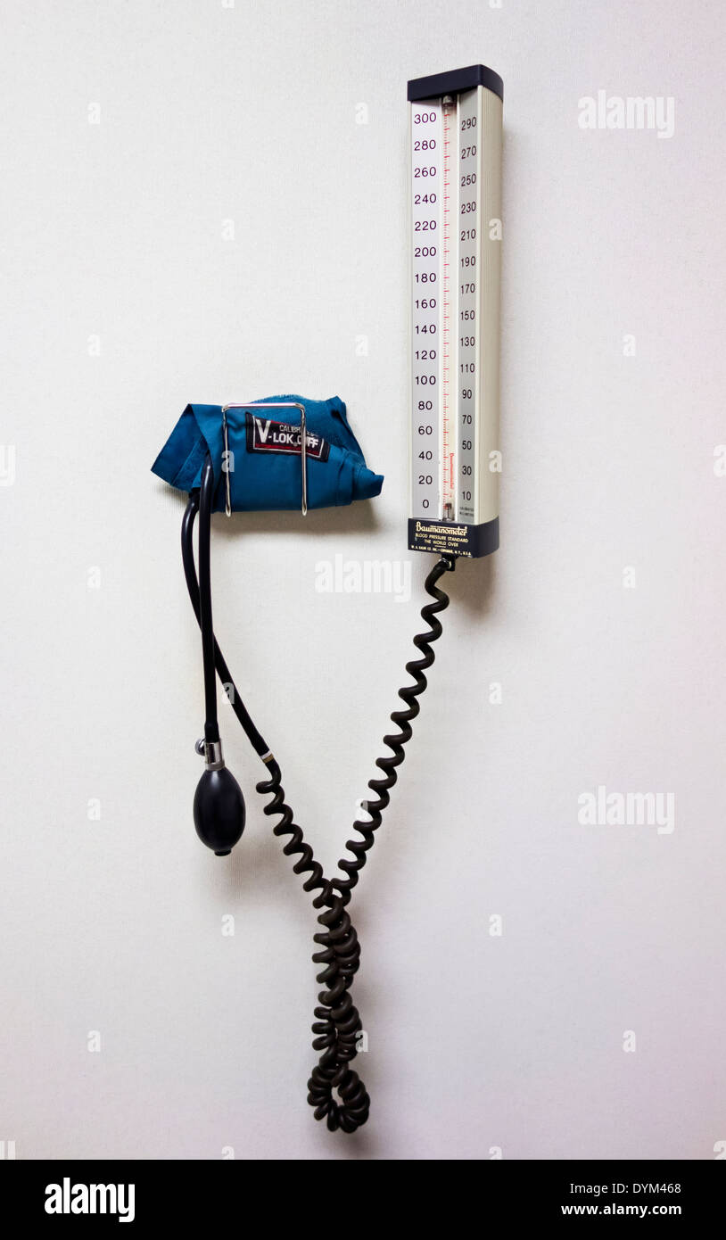 Manual equipment for measuring blood pressure on wall in medical doctor's office.  Cuff and gauge, manometer. - Stock Image