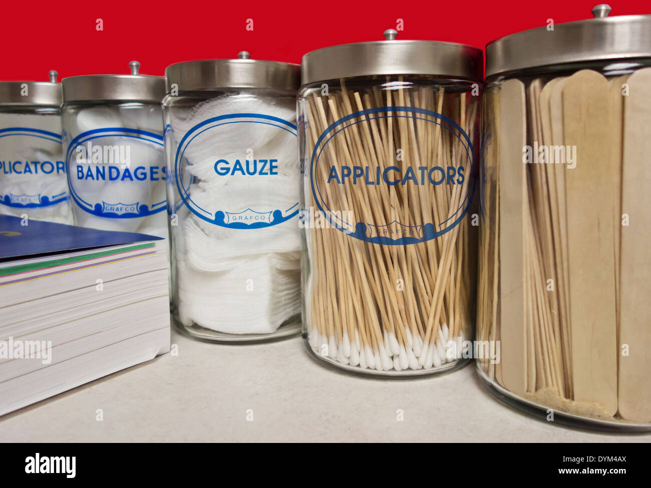 Row of glass containers of gauze, bandages and tongue depressors and medical book.  Used by the doctor to treat and diagnose. - Stock Image