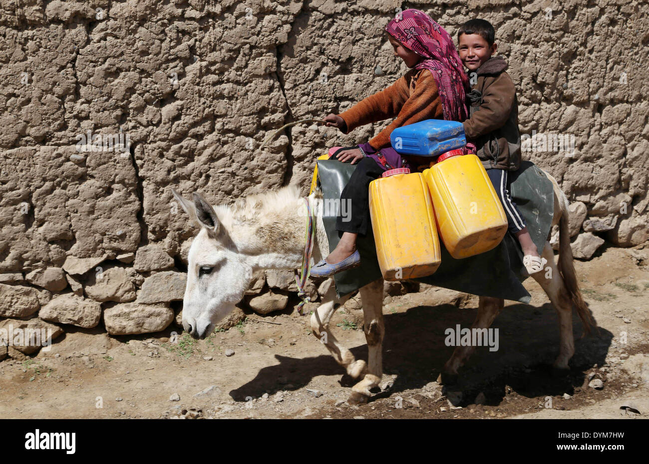 Bamyan. 22nd Apr, 2014. Afghan children ride a donkey while carrying empty barrels to get water in Bamyan province Stock Photo