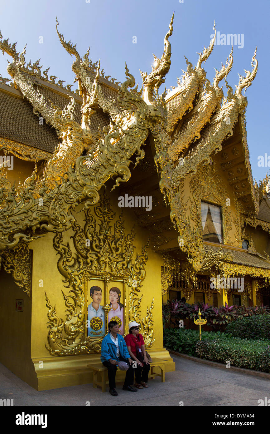 Tourists sitting in front of the gilded toilet house at Wat Rong Khun, White Temple, by architect Chalermchai Kositpipat - Stock Image