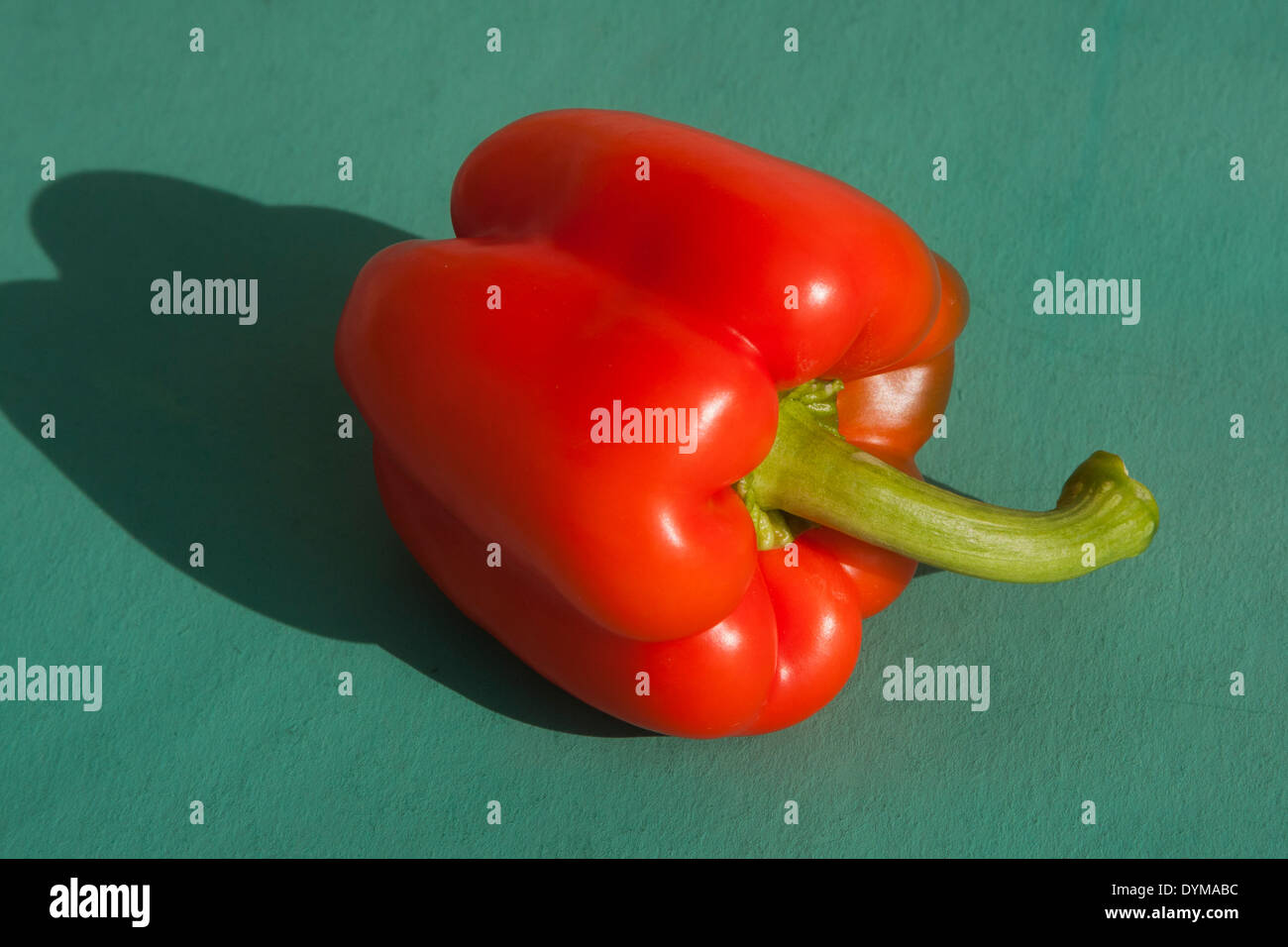 Red Bell pepper on green background - Stock Image